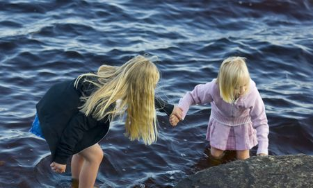 Wading with the helping hand of your sister in a lake in Northern Minnesota. Stock Photo - 3454206
