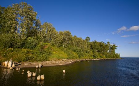north woods: Blue river mouth and the green forest of the North Woods of Minnesota along the shore of Lake Superior. Stock Photo
