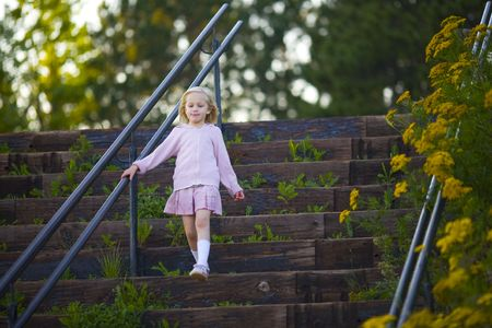 A child descending a large staircase overgrown with weeds and flowers Stock Photo - 3476903
