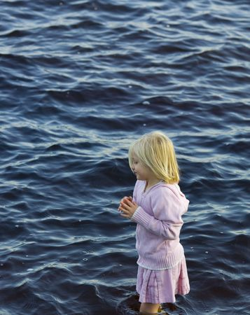 Girl in pink wading through the waters of Island Lake in Northern Minnesota. Stock Photo - 3476901