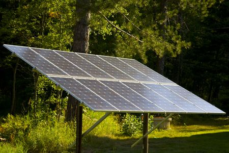 A large solar panel in a forest sunbeam on a summer morning.