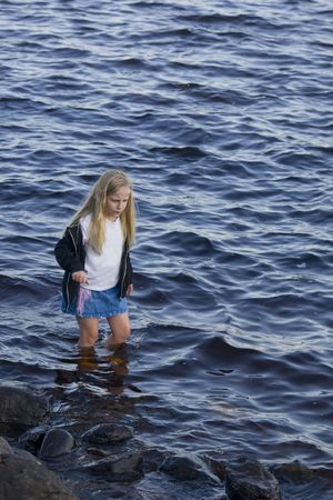 A girl concentrating on not slipping while wading.