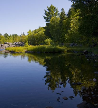 The still shoreline of the St. Louis river in northern Minnesota in green and blue Imagens