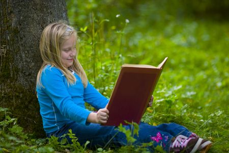 A girl reading under a tree in a green outdoor scene Stock Photo - 3625740