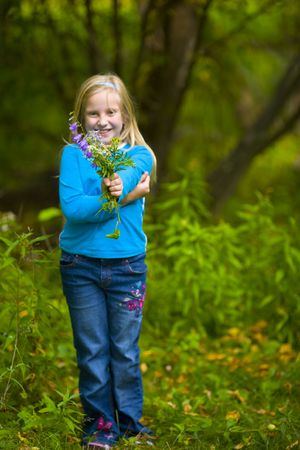 Wildflowers presented by girl in blue in a green forest Stock Photo - 3625738