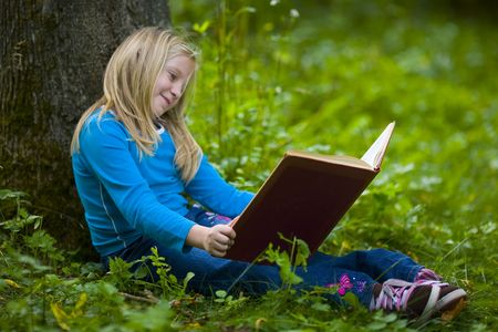 A girl contemplating a good book outdoors under a big tree Imagens