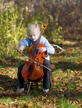 Child player her cello outside on an October afternoon. Stock Photo