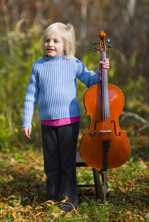 A child standing with her cello outside on a crisp autumn day. Stock Photo