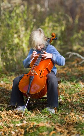 violoncello: Child playing cello pizzicato (plucked) outside on an october afternoon. Stock Photo