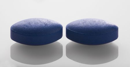 Two blue pills in a close up image.