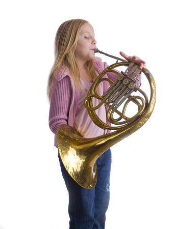 Girl playing an old French horn while standing