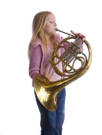 Meisje speelt een oude Franse hoorn terwijl