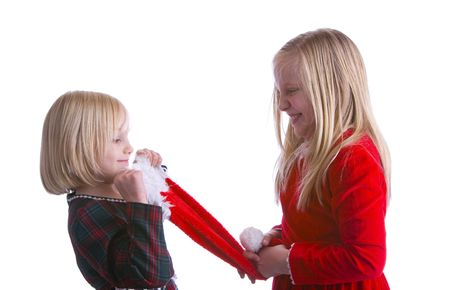 Girls fighting over a santa hat in Christmas dresses Imagens