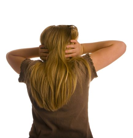 A girl with her back turned and ears covered.