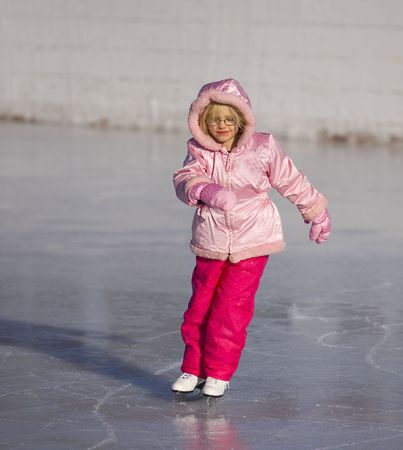 Child in pink ice skating and leaning into a curve Imagens