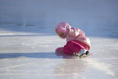 Child falls while ice skating in a pink snowsuit Imagens