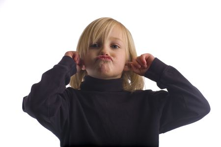 arrogant teen: Child plugging ears and pouting in a black shirt isolated