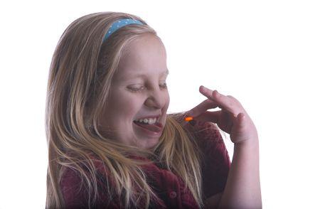 yuck: Girl cringing while holding orange pill trying to take awful medicine