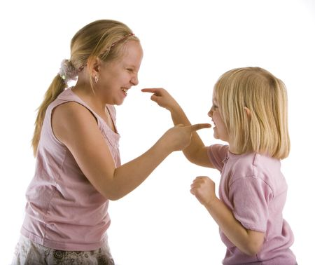 Sisters arguing with pointed fingers wearing pink Stock Photo