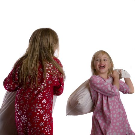 Hermanas con una lucha de almohadas en un fondo blanco Foto de archivo - 4091751