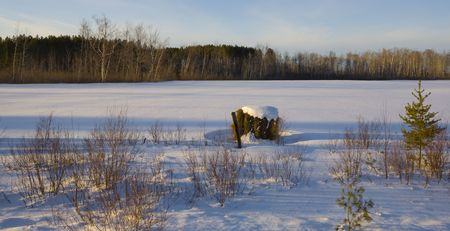 north woods: Hay bale in a snow covered field in the north woods of Minnesota