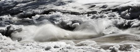 Thawing creek rushing through snow in the North Woods of Minnesota Imagens