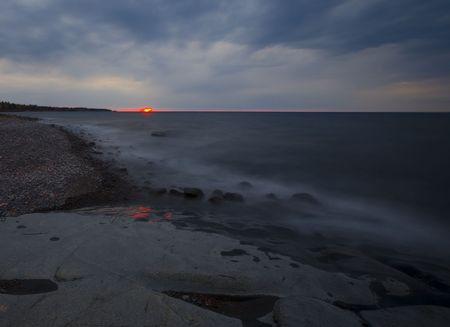 stoney point: Dawn piercing through a morning storm on Stoney Point along the north shore of lake superior in Minnesota