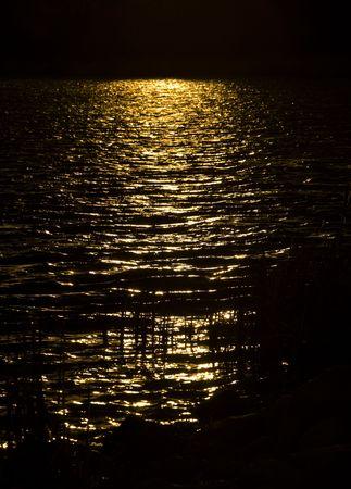 Golden sunbeam on dark lake in the northern Minnesota