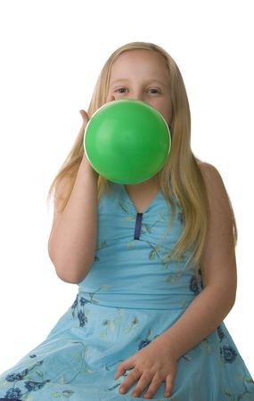 Girl in a blue dress blowing up a green balloon