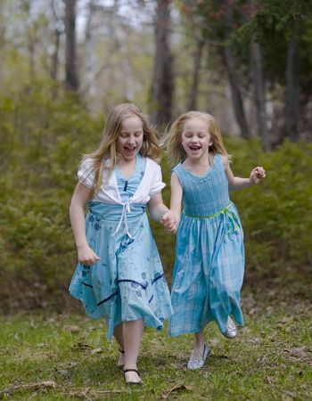 Sisters running in blue spring dresses in the north woods of Minnesota