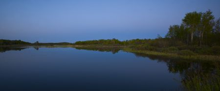 north woods: Night falls on a still blue lake and a green shore at Island lake in the north woods of minnesota