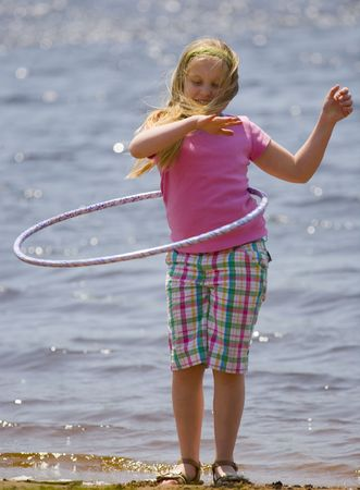 Girl with plastic hoop on beach in a tight shot
