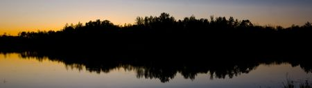 North woods silhouette in the still water of Island Lake in Northern Minnesota