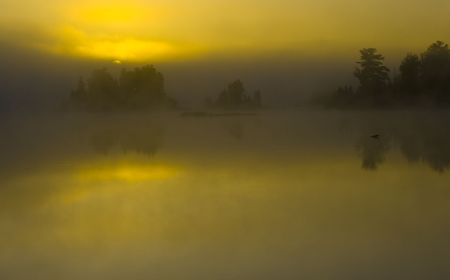 obscured: Dawn obscured by cloud and fog on Boulder Lake in Northern Minnesota Stock Photo