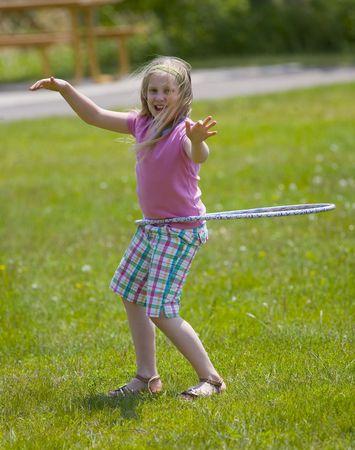 Plastic hoop girl in a park in the summertime Imagens