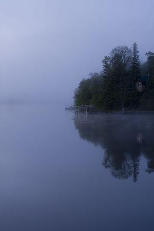 Shoreline in fog before dawn on Island Lake in Northern Minnesota Stock Photo