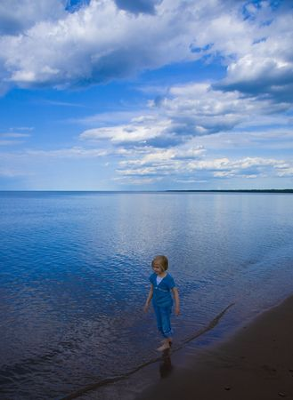 Child, clouds, beach, and blue  reflecting water on Wisconsin Point along the shore of Lake Superior
