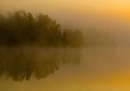 Shoreline hidden in fog at sunrise on Boulder Lake in Northern Minnesota