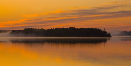 Golden dawn, clouds, and fog on Island Lake in Northern Minnesota