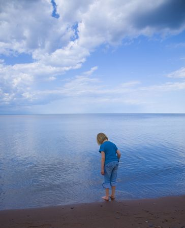Blue child, sky, and water on the Wisconsin shore of Lake Superior