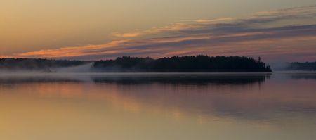 Dawn chasing the fog across Island Lake in Northern Minnesota Stock Photo
