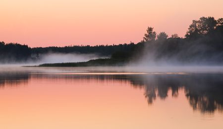 Mist moves through a still morning in a sunrise scene from Fish Lake, Minnesota Stock Photo