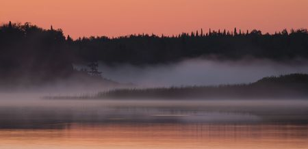 Salmon sky and foggy water for sunrise at Fish Lake Minnesota