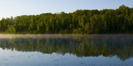 Morning reflecting forest at Deep Water Lake Minnesota Stock Photo