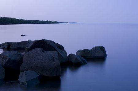 Twilight, glass water, and stone on the North Shore of Lake Superior Stock Photo