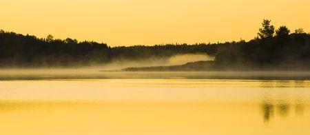 Sunlight on mist and water at Fish Lake Minnesota Stock Photo