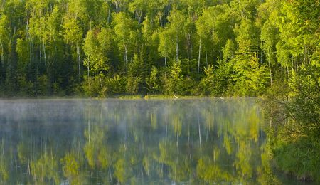 Mist dances with the morning forest on Deep Water Lake in Northern Minnesota Stock Photo
