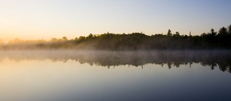 Sunrise burns away the morning mist at Boulder Lake in Northern Minnesota