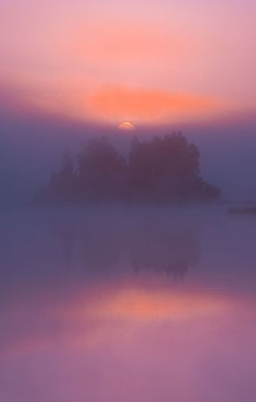 Fog and reflection in violet sunrise on Boulder Lake in Northern Minnesota Stock Photo