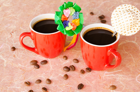 black wreath: Black coffee in two red cups with a hat and a wreath